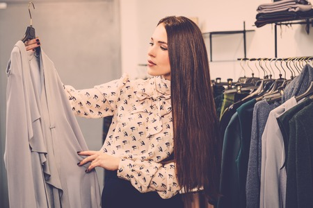 clothing rack: Young woman choosing clothes on a rack in a showroom
