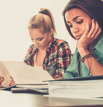 final: Girls students preparing for exams in apartment interior behind table Stock Photo