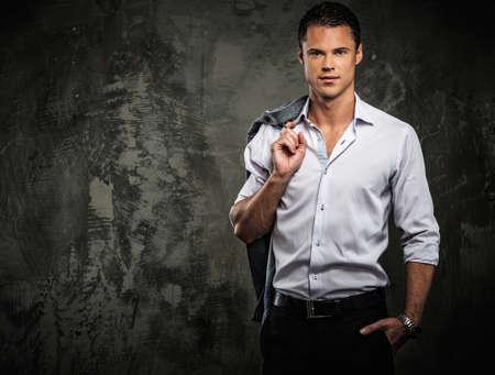 Bel homme en chemise contre le mur grunge tenant veste sur l'épaule Banque d'images