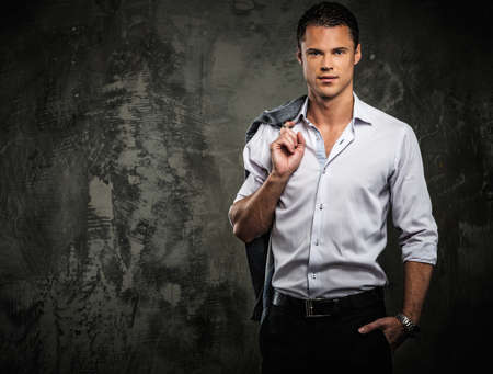 riches: Handsome man in shirt against grunge wall holding jacket over shoulder