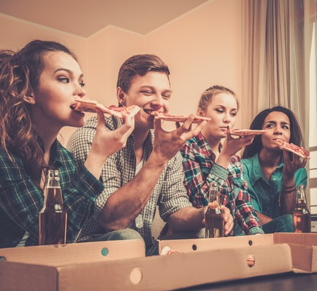 Group of young multi-ethnic friends with pizza and bottles of drink celebrating in home interior photo