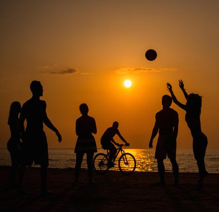 beach volleyball: Silhouettes a young people playing with ball on a beach Stock Photo