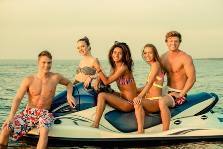Group of happy multi ethnic friends sitting on a jet ski photo