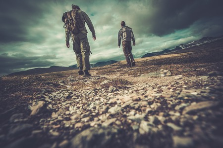 Two hikers walking in a valley photo