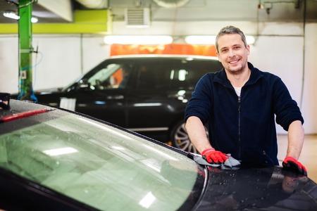 lavarse las manos: Trabajador Alegre limpiando coche en un t�nel de lavado