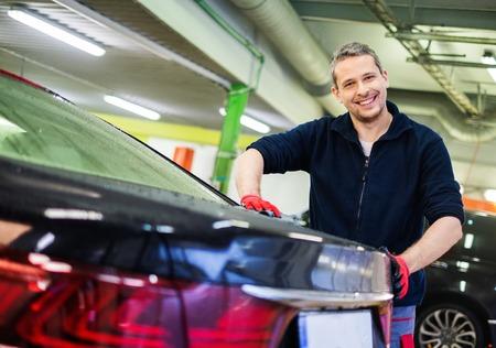 autolavaggio: Lavoratore allegro asciugandosi auto su un autolavaggio