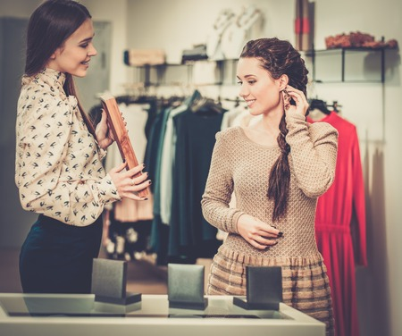 jewellery: Young woman choosing jewellery with shop assistant  help