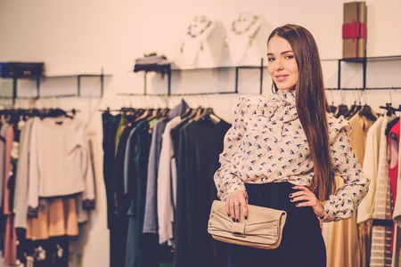 designer bag: Fashionable young woman in a fashion showroom