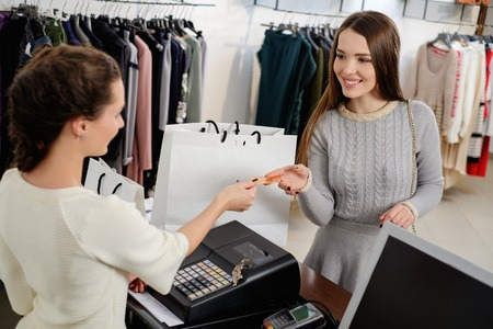 pay desk: Happy woman customer paying with credit card in fashion showroom Stock Photo
