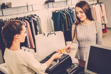paying with credit card: Happy woman customer paying with credit card in fashion showroom Stock Photo