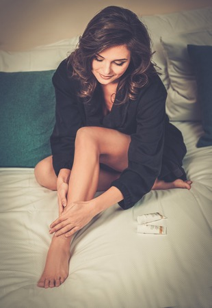 moisturiser: Woman applying moisturiser cream on her legs