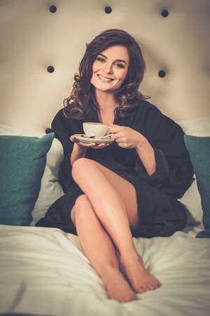 vacation home: Woman with coffee on a bed in a hotel room