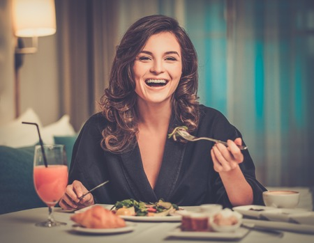 Beautiful woman having breakfast in a hotel room photo