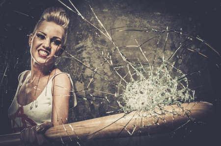 punk: Punk girl breaking glass with a baseball bat Stock Photo