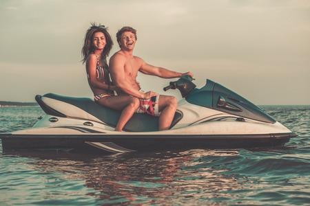 Multi ethnic couple sitting on a jet ski photo