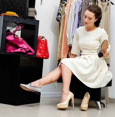 choosing clothes: Young woman choosing shoes in a showroom Stock Photo