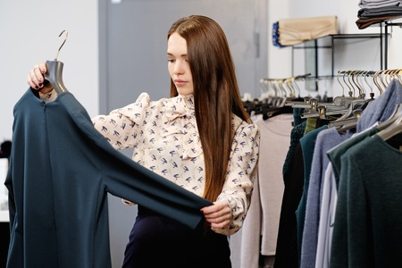 changing clothes: Young woman choosing clothes on a rack in a showroom