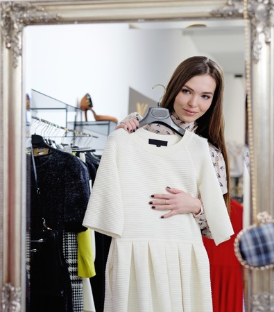 choosing clothes: Young woman choosing clothes in a showroom