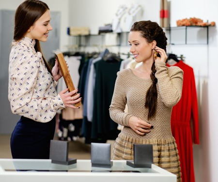 Young woman choosing jewellery with shop assistant  help photo