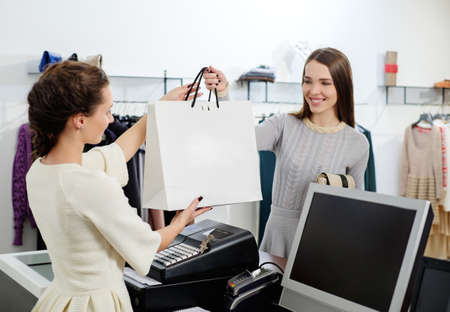 checkout: Happy customer with shopping bag in fashion showroom Stock Photo