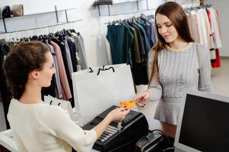 tienda de ropa: Cliente mujer feliz pagando con tarjeta de crédito en el showroom de moda Foto de archivo