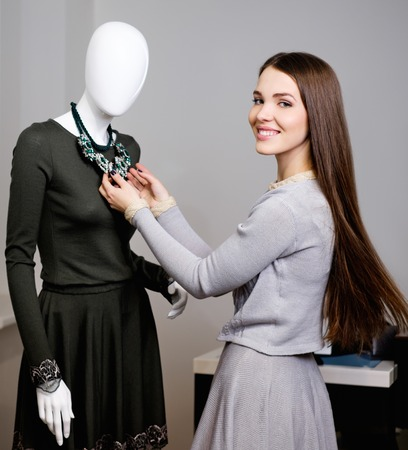 Young woman looking at necklace on mannequin in showroom photo