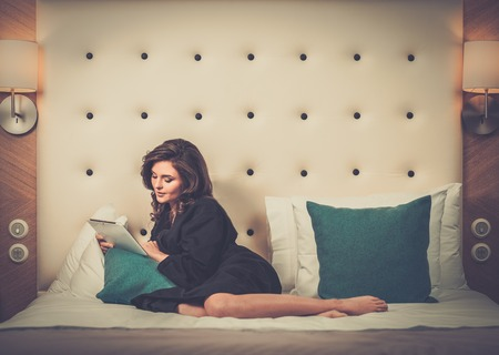 Woman in bathrobe lying on a bed with tablet pc photo