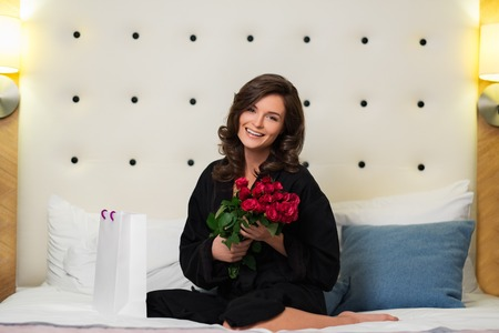 Woman with bunch of roses and gift bag on a bed in hotel room photo