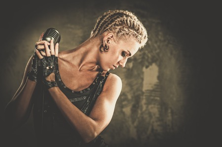 Attractive steampunk singer with microphone photo