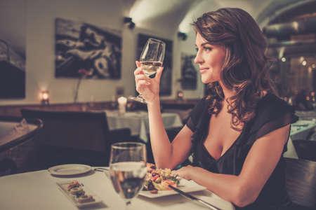 Señora joven hermosa sola en restaurante