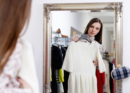 clothing rack: Young woman choosing clothes in a showroom