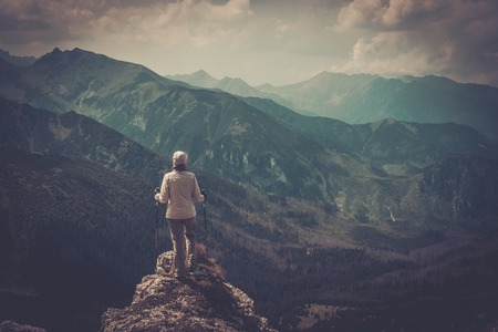 Woman hiker on a top of a mountain photo