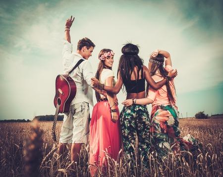 mujer hippie: Amigos hippies multiétnicos con la guitarra en un campo de trigo Foto de archivo