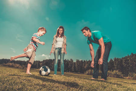 women playing soccer: Happy young family playing football outdoors