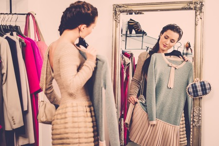 Young woman choosing clothes in a showroom photo