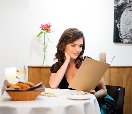 carte: Beautiful young lady choosing food in restaurant Stock Photo