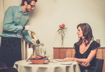 Waiter offering wine to lady in restaurant photo