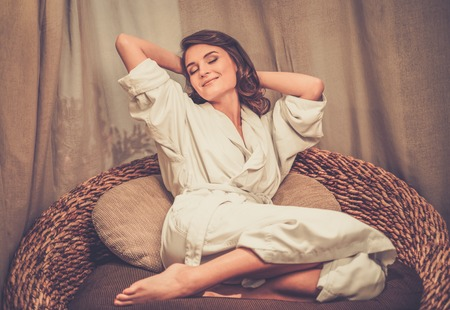 Beautiful woman relaxing in a bathrobe in spa salon Stock Photo