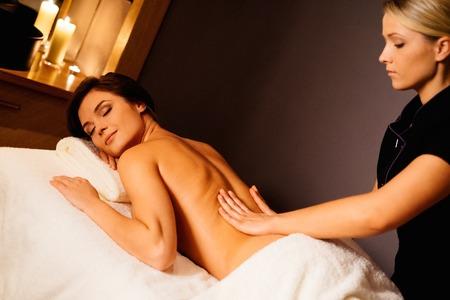 Beautiful young woman having massage in a spa salon photo