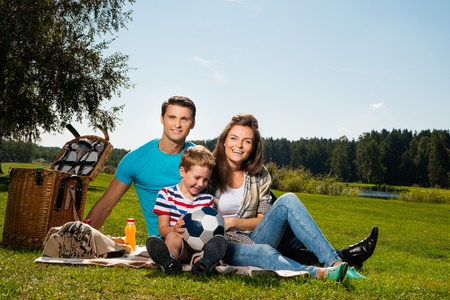 family on grass: Young family having picnic outdoors Stock Photo
