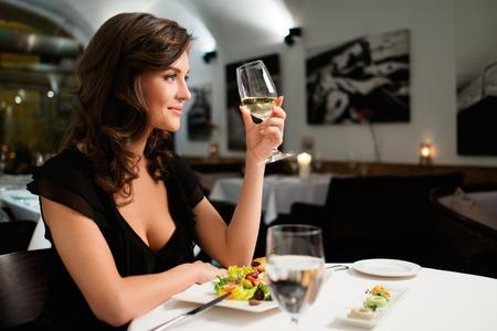 mujer sentada: Señora joven hermosa sola en restaurante