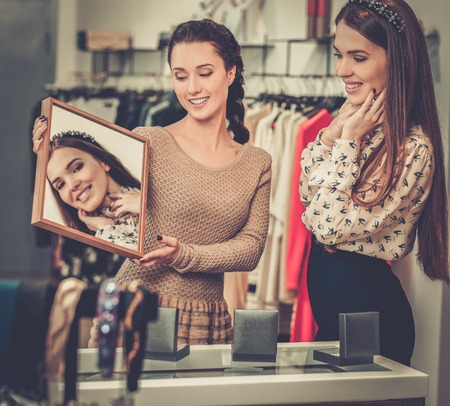 choosing clothes: Young woman choosing jewellery with shop assistant  help