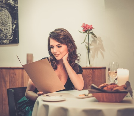 Beautiful young lady choosing food in restaurant photo