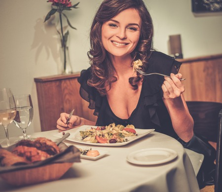 Beautiful young lady alone in restaurant photo