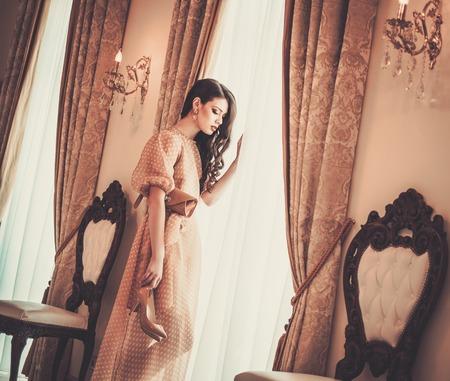 Woman near window in luxury house interior photo