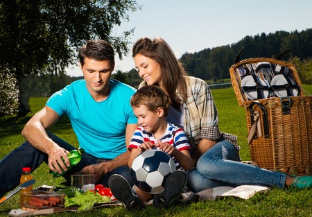 familia comiendo: Familia joven con comida campestre al aire libre