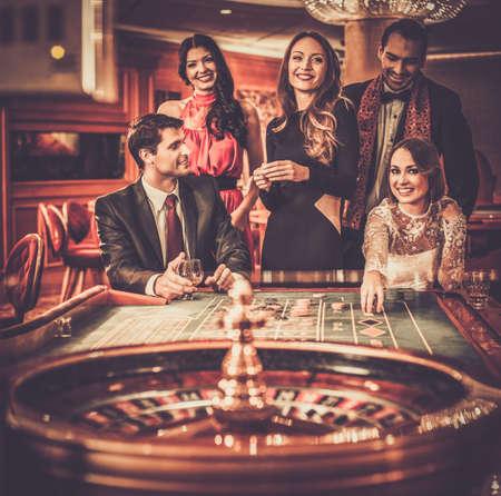 roulette: Gruppo di persone eleganti che giocano in un casinò