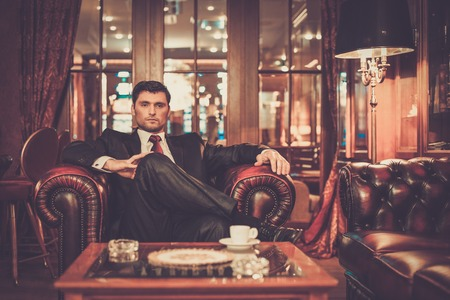 Confident handsome brunette sitting in luxury interior photo