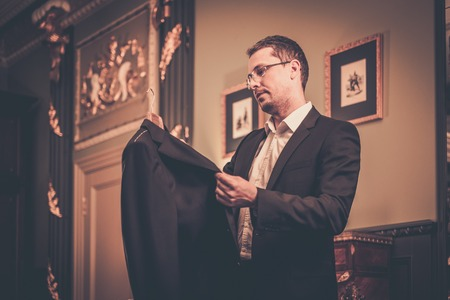 Middle-aged man looking at suit on a hanger photo