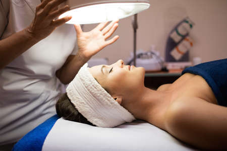 treatment: Young woman having facial treatment Stock Photo